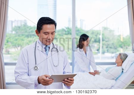 Doctor using digital tablet when nurse talking to senior patient