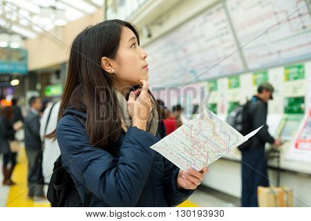 Confused woman look for direction in train station