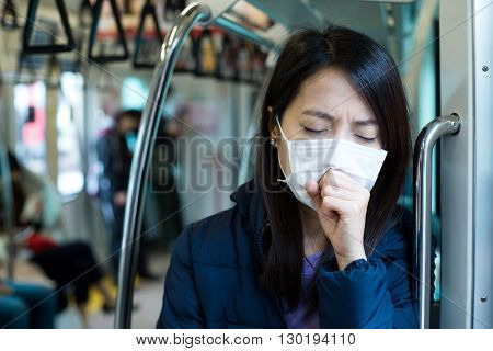 Woman wearing face mask in train compartment