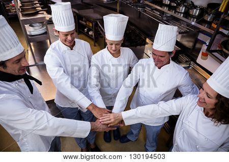 Team of chefs putting hands together and smiling in a commercial kitchen