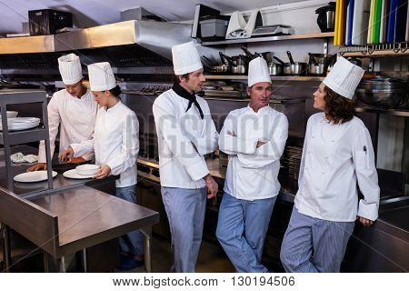 Team of chefs standing together in commercial kitchen and interacting