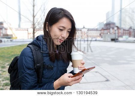 Woman use of cellphone and holding a coffee cup