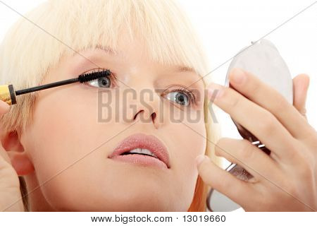 Portrait of pretty young woman applying mascara using lash brush