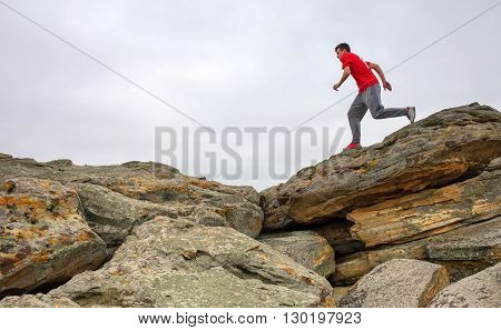 Sport man running jumping over rocks in mountain area. Fit male runner exercise training and jumping outdoors in beautiful nature