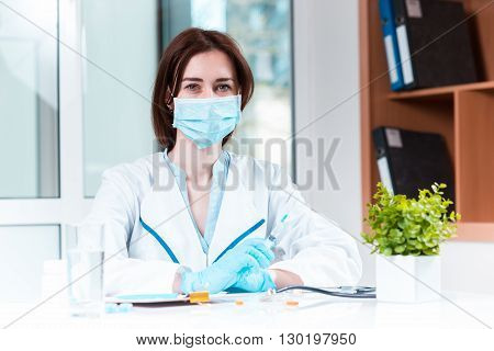 The hand of female doctor in blue glove holding syringe against white medical gown