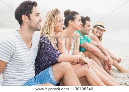 Group of happy friends sitting side by side on the beach