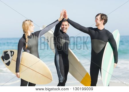 Happy surfer giving high-five to each other on the beach on a sunny day