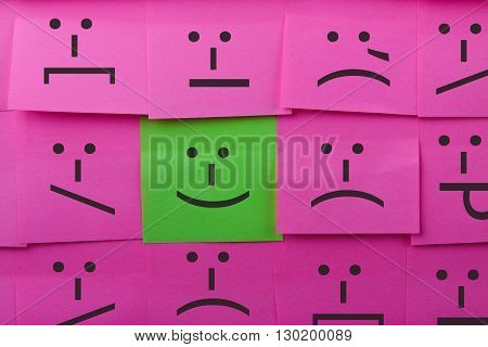 Emotions concept. Background of sticky notes. Green sticky note is among pink sticky notes.