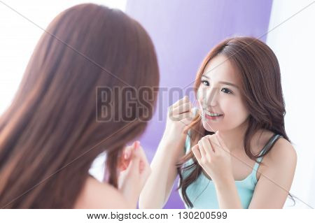 Close up of Smile woman clear teeth by floss and look mirror. great for health dental care concept. asian beauty