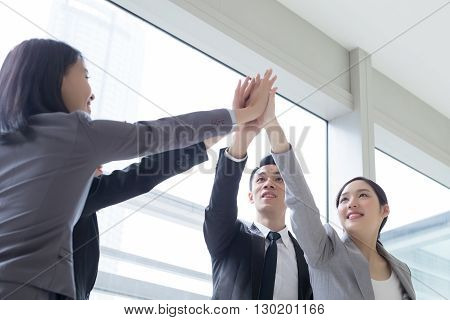 Business people team smile give high five in the office shot in Hong Kong asian woman and man