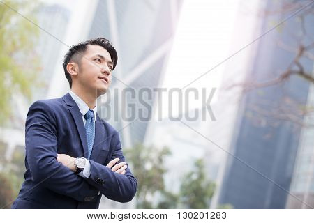 Business man smiles looks  at sky with business office building background asian shot in Hong Kong