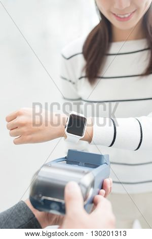 young woman pays by smart watch with empty screen great for your design asian beauty