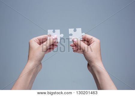 The puzzles in hands on gray background