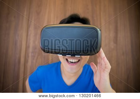 Happy man getting experience using VR-headset glasses of virtual reality at home much gesticulating hands asian male