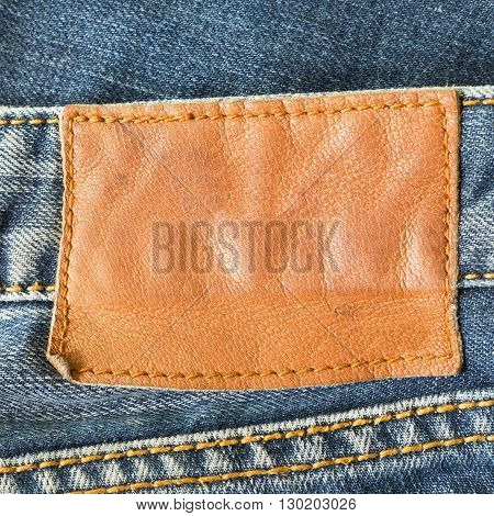 brown leather tag on blue jeans, clothing industry