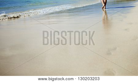 Footprints in the sand, a woman walks along the shore