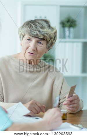 Older and sick woman taking her pills