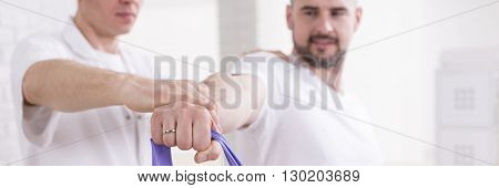Handsome man exercising with a professional instructor holding tape for stretching panorama