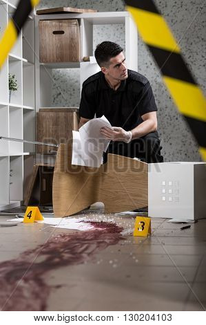 Policeman during work standing behind yellow crime scene tape