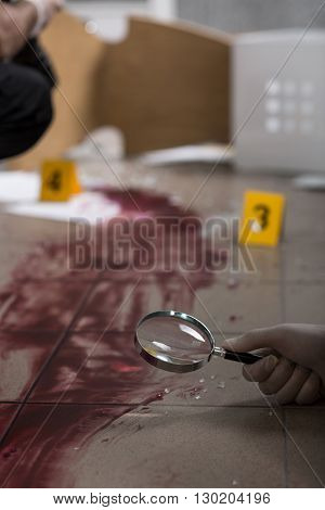 Close up of a bloody splash and hand holding a magnifier
