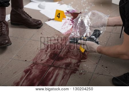 Policeman holding evidence bag with a gun close up of a bloody splash