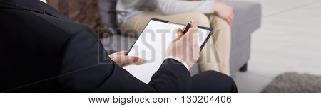 Close up of a psychoanalyst doing notes in the background patient sitting on a sofa