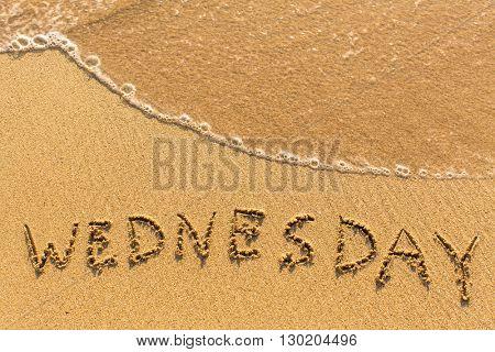 Wednesday - inscription by hand on a light-golden beach sand.