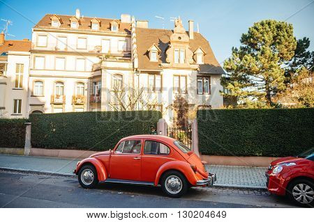 STRASBOURG FRANCE - 25 DEC 2016: Vintage red Volkswagen Beetle car on the street of Strasbourg France with beautiful houses in the background