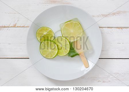 Lime popsicle on white wooden table background