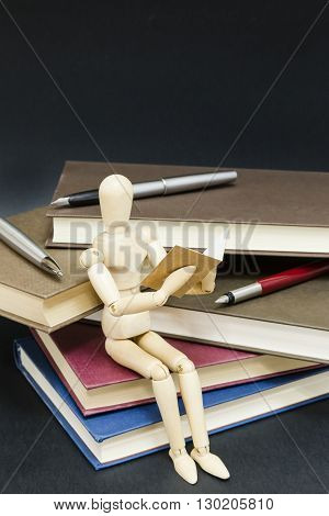 maniqui reading sitting on a mountain of books and pens with a black background
