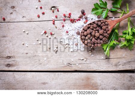 Seasoning for cooking. Allspice pepper in wooden spoon and sea salt red pepper and herb parsley on aged wooden background. Food ingredient. Selective focus. Place for text. Flat lay. Top view.