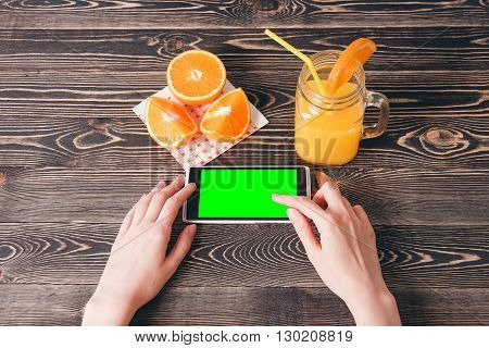 Woman Using Mobile Phone against Fruits Oranges on Wooden Background. Technology Concept.