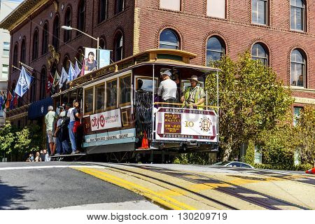 SAN FRANCISCO - OCT 06: Passengers enjoy a ride in a cable car on Oct 06 2012 in front of famous Transamerica building in San Francisco. It is the oldest mechanical public transport in San Francisco which is in service since 1873.
