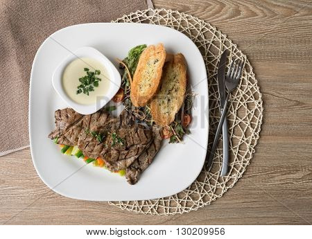 Beef filet steak served with bread vegetables mushroom and mustard sauce on white porcelain dish on wooden table