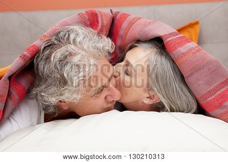 Closeup Of Mature Woman Kissing His Partner In Bed At Home