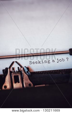 Seeking a job message on a white background against close-up of typewriter