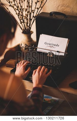 Gratitude message on a white background against rear view of a woman is using a writing machine