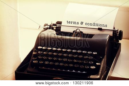 Terms and conditions message on a white background against typewriter on a table