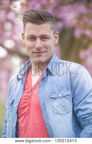 portrait of handsome man in front of cherry blossom