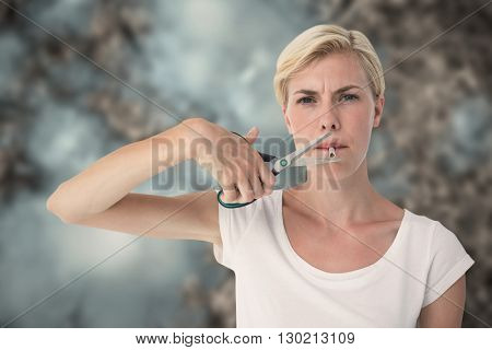 Attractive blonde woman cutting cigarette with scissors against grey background