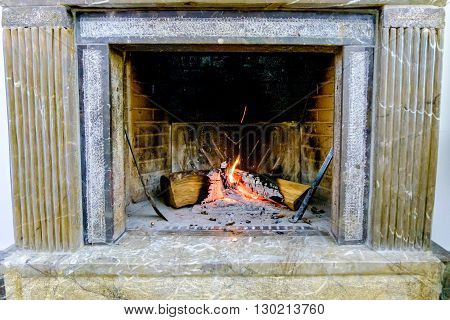 Domestic Marble chimney with burning wood. Italy