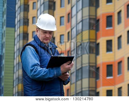 Engineer standing against the background of a new block of flats. The house is built and renting houses. Engineer in a helmet with papers in hand