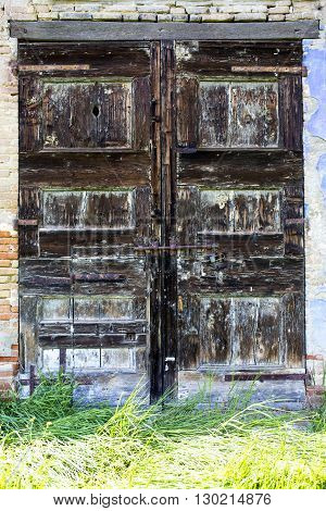 Old door of an abandoned farmhouse .