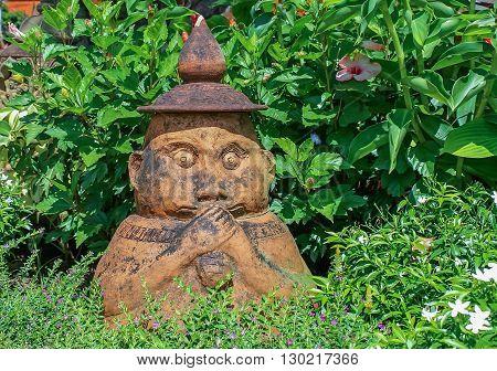 Little Buddha eating bread ceramic statue. Buddhism, yoga, meditation concept