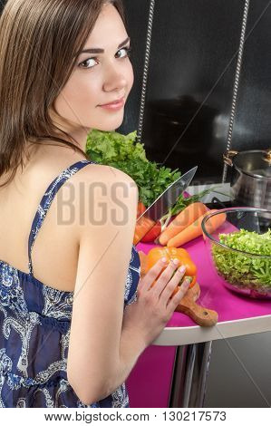 Portrait of a beautiful young woman standing in the kitchen with his back to the camera and the cooking salad