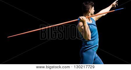 Rear view of sportsman practising javelin throw