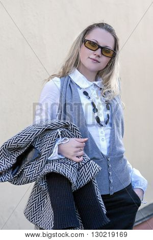 Portrait of Fashionable Caucasian Blond Woman.Posing With Trendy Coat and Wearing Sun glasses Outdoors. Vertical Shot