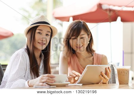 Korean female friends sitting in cafe after shopping