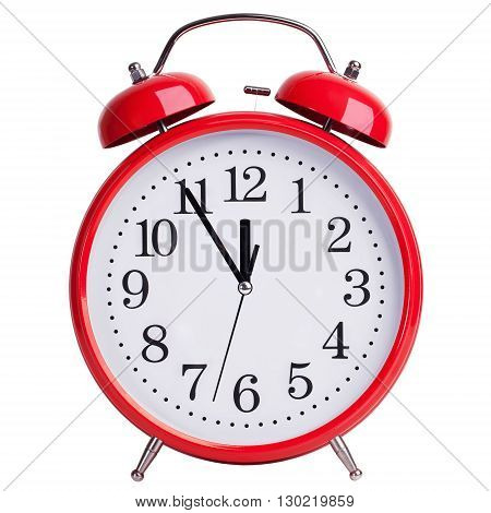 Red round alarm clock shows five minutes to twelve