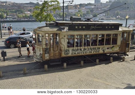 PORTO, PORTUGAL - AUGUST 19, 2016: People in the vivinity of a historical tram parked on the street next to the river Douro in Porto Portugal.